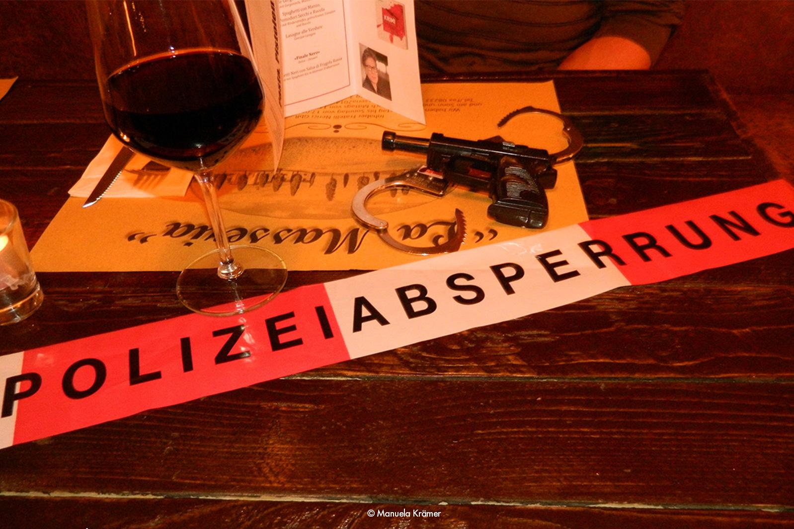 Tisch mit Weinglas, Absperrband und Pistole aus der Lesung mit Manuela Krämer