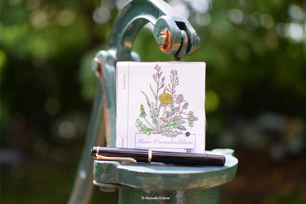 """Ein selbstgemachtes """"Wiesenbüchlein"""" aus der Grundschule und ein Füller steht als Symbol für Whitepaper, die Texterin Manuela Krämer schreibt."""