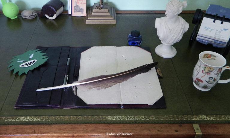 Feder, Schreibunterlage, Tasse, Tintenfass, Papiermonster auf einem antiken Schreibtisch als Symbol für gute Artikel und Beiträge
