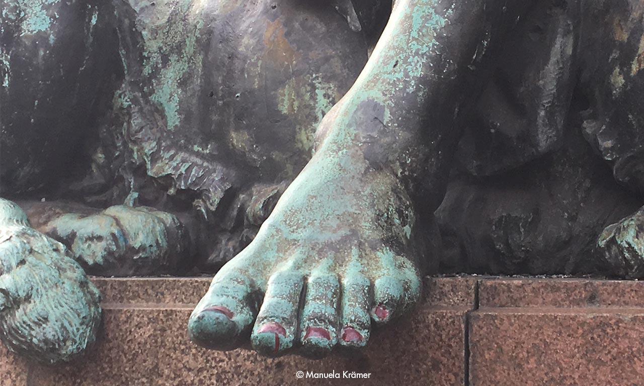 Fuß einer Bronzeskulptur mit lackierten Nägeln - guter Content, weil anders.
